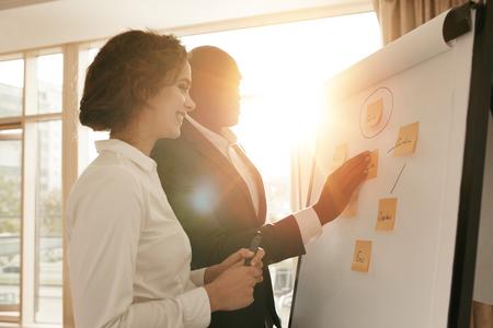 sala de reuniones: Dos colegas de negocios que trabajan en proyecto juntos. La gente de negocios poniendo sus ideas en la pizarra durante una presentación en la sala de conferencias.