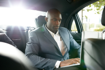 black business man: Shot of happy young businessman traveling to work in the luxury car on the back seat and using laptop. African business associate working inside the car. Stock Photo