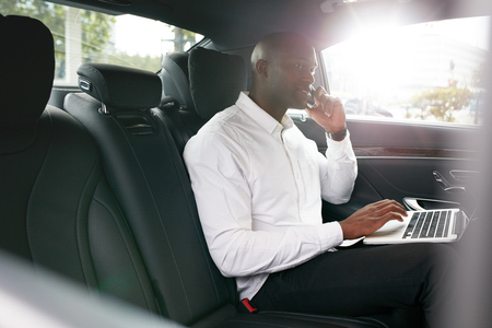 african business: Businessman with laptop receiving a phone call on the backseat of a car. African businessman working during travelling to office in a luxury car. Stock Photo