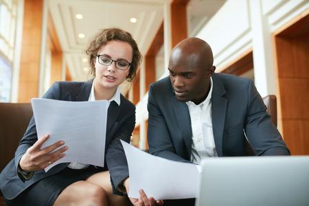 Portret van jonge zaken man en vrouw zitten in cafe en bespreken contract. Diverse ondernemers bijeenkomst in hotel lobby lezen van documenten.