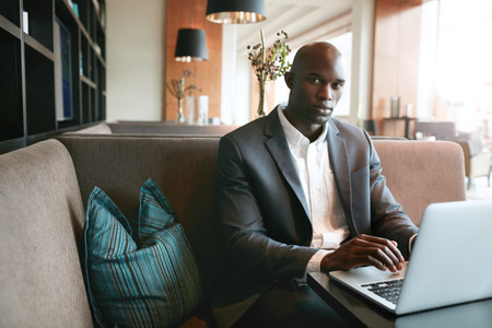 man working computer: Portrait of young african businessman working on laptop in cafe. man sitting on hotel coffee shop.