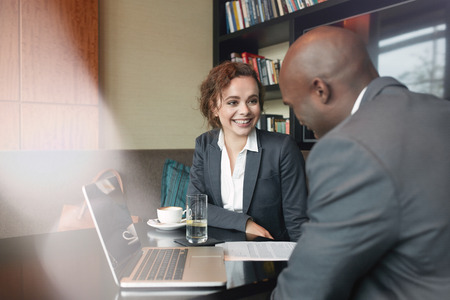 client meeting: Two business partners sitting in cafe and discussing business plan. Businessman and businesswoman smiling during meeting in a coffee shop. Stock Photo