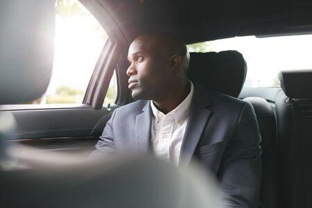 persona viajando: Hombre de negocios africano joven que viaja para trabajar en el coche de lujo en el asiento trasero mirando fuera de la ventana.