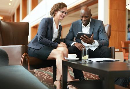 reunion de trabajo: Dos hombres de negocios sentado en la cafetería que discute proyecto sobre la tableta digital. Empresaria joven y hombre de negocios mirando la computadora tablet sonriendo.