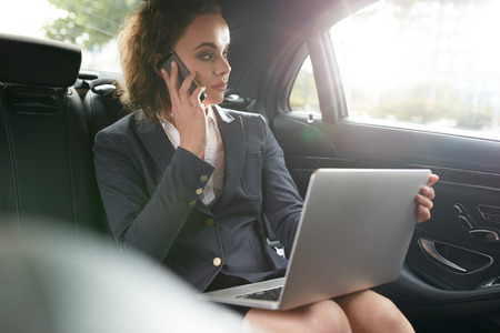 Businesswoman sitting on back seat of car with laptop talking on mobile phone. Female executive travelling to work in luxury car. Stock Photo