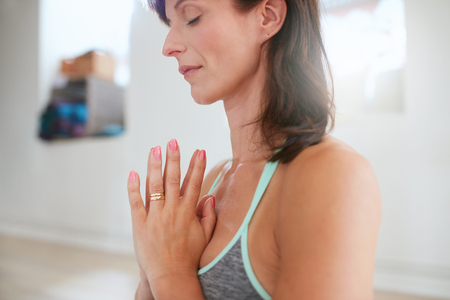anjali: Woman meditating with hands together. Close up shot of mature woman doing yoga.