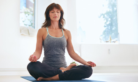 legs crossed at knee: Woman sitting on exercise mat in lotus position with her eyes closed doing yoga. Fit caucasian female practicing Padmasana at gym.