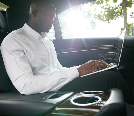 inside: Shot of young african businessman working on laptop inside a car. Business associate travelling to work in a car. Stock Photo