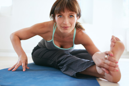 mature female: Beautiful woman sitting in Triang Mukha Eka Pada Paschimottanasana. Three-Limbed Forward Bend pose. Fit woman stretching yoga posture.