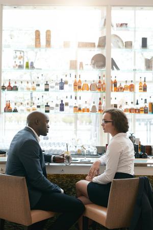 barra de bar: Retrato de jóvenes empresarios sentados juntos en el café. Hombre de negocios y reunión mujer en el café después del trabajo. Foto de archivo