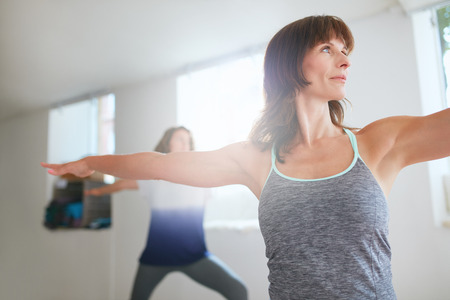 selective focus: Shot of fitness woman doing yoga. Women exercising at yoga class. Virabhadrasana pose.