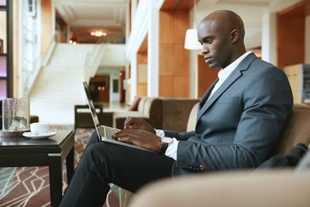 réseautage: Image de jeune homme d'affaires occupé à travailler sur ordinateur portable. Homme d'affaires afro assis dans le hall de l'hôtel en attendant quelqu'un. Banque d'images