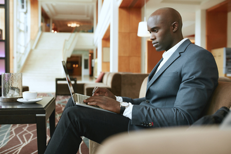 serious: Image of busy young businessman working on laptop. African businessman sitting in hotel lobby waiting for someone. Stock Photo