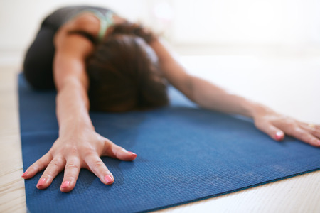 zen: Woman stretching forward, performing a yoga pose on exercise mat. Fitness female performing balasana yoga at gym, focus on hands.