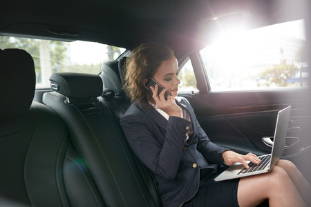 Businesswoman with laptop receiving a phone call on the backseat of a car. Female entrepreneur working during travelling to office in a luxury car.