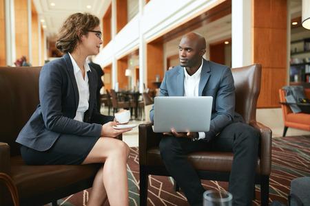 dos personas platicando: Retrato de dos colegas empresarios sentados en la cafeter�a. Hombre de negocios africano con ordenador port�til y de negocios con la taza de caf� que discute el trabajo. Foto de archivo