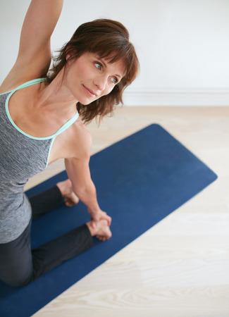 mujer arrodillada: Retrato de la mujer de la aptitud Ustrasana pose de yoga que mira lejos. Hembra cauc�sica practicar ejercicios de yoga en el gimnasio. Camel Pose.