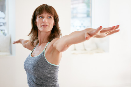 mature brunette: Portrait of mature woman stretching her arms and looking away at gym. Beautiful woman performing yoga in warrior pose, Virabhadrasana.
