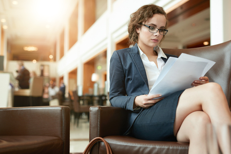 woman shop: Portrait of busy young woman reading contract documents. Businesswoman sitting at cafe going through business reports.