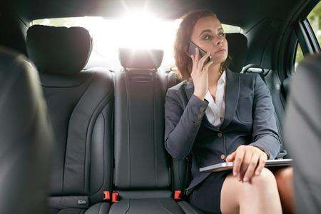 secretaria: Empresaria con el teléfono móvil en el asiento trasero de un coche. Asociado Mujer haciendo una llamada telefónica durante el viaje al trabajo.