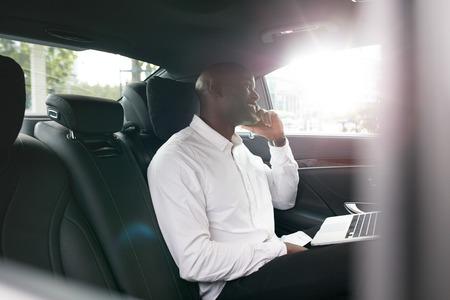 Afrikaanse zakenman met laptop praten over de mobiele telefoon in de auto. Jonge ondernemer werken tijdens het reizen naar het kantoor in een luxe auto. Stockfoto