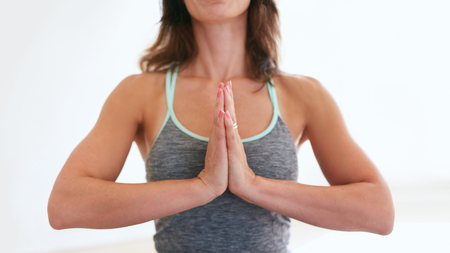Cropped image of fitness woman practicing yoga in gym. Female fitness trainer sitting with her hands joined meditating at health club.