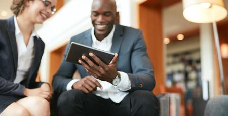 Happy jonge mensen uit het bedrijfsleven bij elkaar zitten met behulp van digitale tablet, terwijl in het hotel lobby. Focus op tablet-computer. Stockfoto