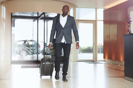 Empresario caminando en el vestíbulo del hotel. Retrato de cuerpo entero de la joven ejecutivo africano con una maleta.