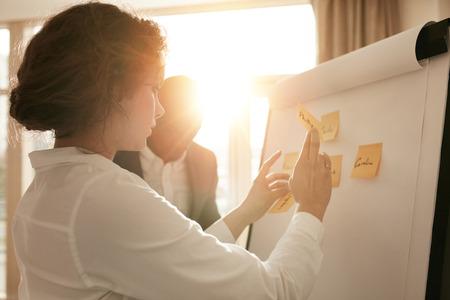 Schot van jonge professionals brainstormen in een vergadering. Zakenvrouw en zakenman presenteren hun ideeën op whiteboard.