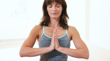 anjali: Portrait of healthy woman practicing meditation yoga. Mature caucasian female sitting at the gym with her hands joined meditating in Anjali Mudra yoga pose.