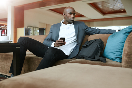 one young man: Shot of african businessman with a mobile phone in hand, sitting on couch looking away. Young business executive waiting in hotel lobby.