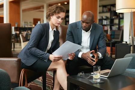mujeres trabajando: Tiro de dos empresarios j�venes sentados juntos en un caf� papeles del contrato de lectura. Los ejecutivos que se re�nen en un pasillo del hotel.