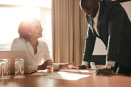 contrato de trabajo: Dos j�venes empresarios reunidos en la sala de conferencias y trabajando en nuevos proyectos. Los compa�eros de trabajo feliz en discusiones sobre nuevas ideas de negocio.