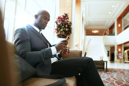 african business: Male executive sitting on sofa looking at his mobile phone. African businessman waiting in hotel lobby.
