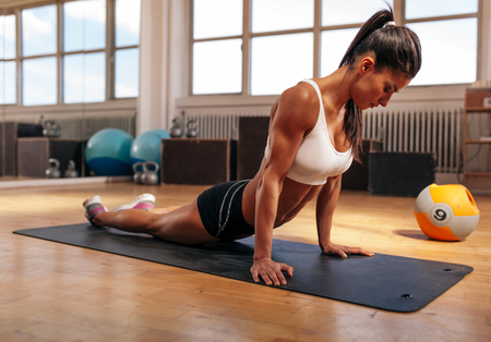 mat: Woman on fitness mat doing stretching exercises at gym. Fit caucasian woman working out at health club. Stock Photo