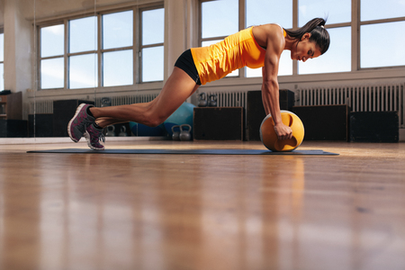 kettlebell: Fit young female athlete working out on her core muscles. Muscular woman exercising on fitness mat doing push ups with kettlebell. Stock Photo