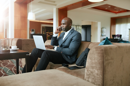 businessman talking: Businessman sitting on sofa with a laptop using mobile phone. Busy african male executive waiting in hotel lobby.