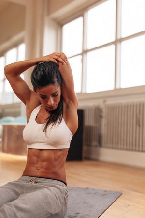 forme et sante: Musculaire jeune femme étirant ses bras derrière son dos au gymnase.