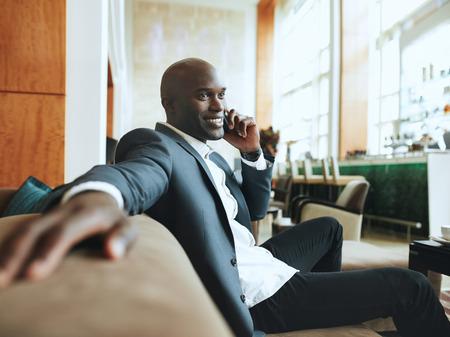 행복 한 젊은 사업가 호텔 로비 누군가를 기다리고, 전화를하고 소파에 편안 앉아.