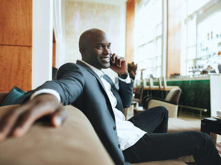 african business man: Happy young businessman sitting relaxed on sofa at hotel lobby making a phone call, waiting for someone.