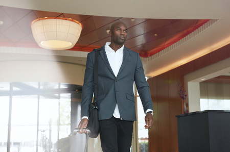 corporate travel: Portrait of young businessman with luggage in hotel lobby. African business executive walking in hotel hallway with his baggage. Stock Photo