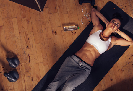 lying on stomach: Top view of relaxing young woman lying on fitness mat. Overhead shot of female athlete resting after intense workout with water bottle, mobile phone and kettle bell on floor.