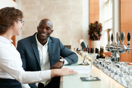 tomando café: Hombre joven feliz que se sienta con la mujer en el mostrador de bar. Pareja de negocios en el café después del trabajo.