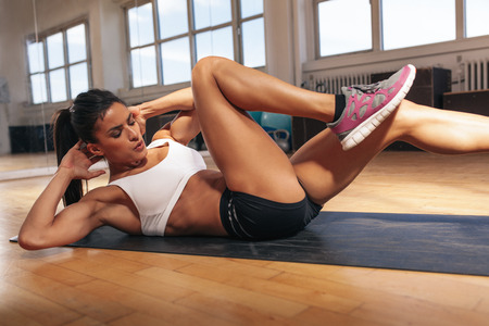 hands on stomach: Young fit woman exercising in a gym lying on mat doing leg raising and twisting exercises. Young attractive woman doing abs workout. Fitness woman doing a sit up.