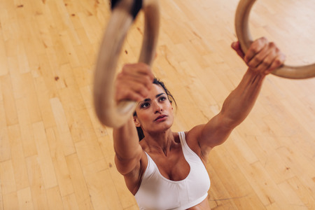 fitness training: Determined young woman at gym. Muscular female athlete working out using gymnastic rings.