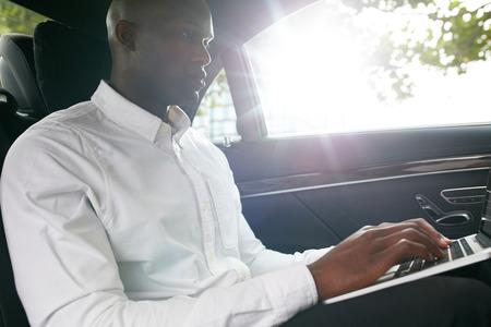detras de: El hombre de negocios que viaja a la oficina en el coche de lujo en el asiento trasero y el trabajo en la computadora portátil.