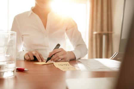 회의실에 앉아있는 동안 스티커 메모에 대한 몇 가지 이름을 쓰는 여자의 자른 샷.
