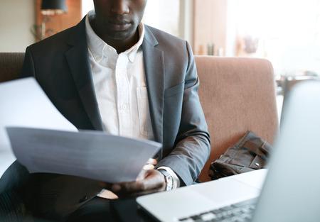 usando computadora: Recortar foto de joven empresario pasando por unos papeles. Ejecutivo de negocios africana lectura de documentos mientras se está sentado en la cafetería.