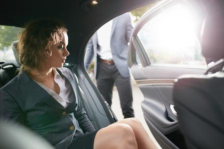 adentro y afuera: Hombre que abre una puerta de pasajeros para una empresaria salir de un coche. Empresario de sexo femenino que viaje a la oficina en un coche de lujo.