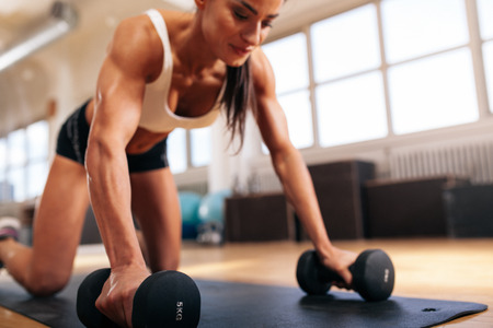 pushups: Woman doing push-ups on dumbbells at the gym, focus of arms of woman.